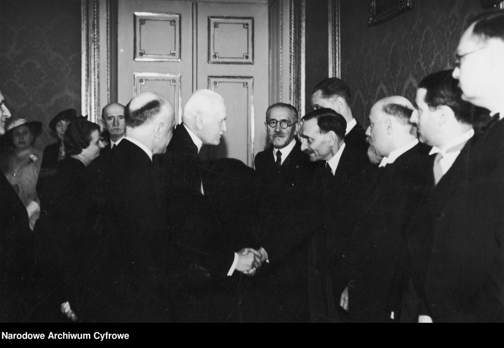grupa mężczyzny ubranych elegancko wita się ze sobą, w tle drzwi. Zdjęcie czarno-białe.