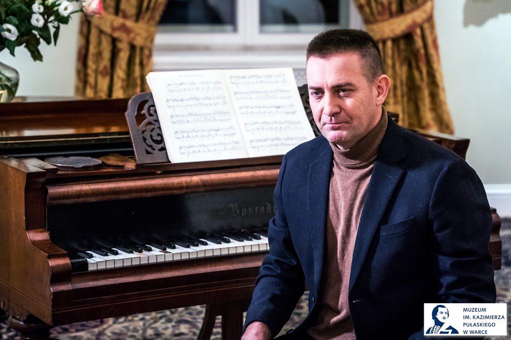mężczyzna siedzący przy fortepianie