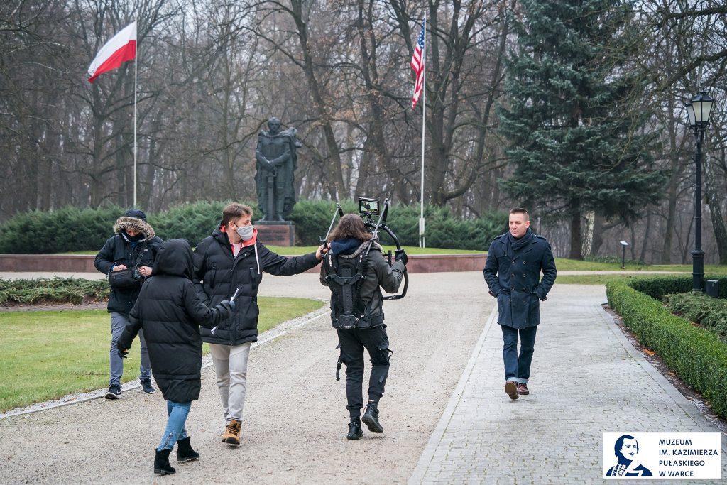 nagruwanie filmu, ekipa idzie tyłem filmując spacerującego aktora w płaszczu