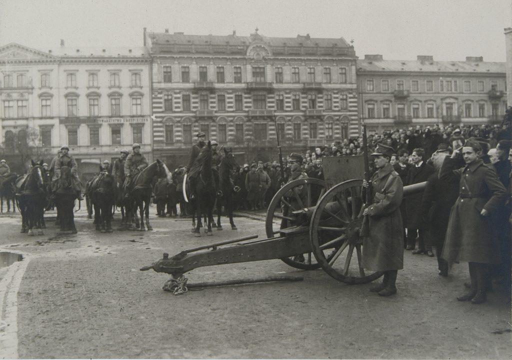 czarno-białe zdjęcie olacu. na pierwszym planie działo, obok zgromadzony tłum i żolnierze na koniach, w tle kamienice