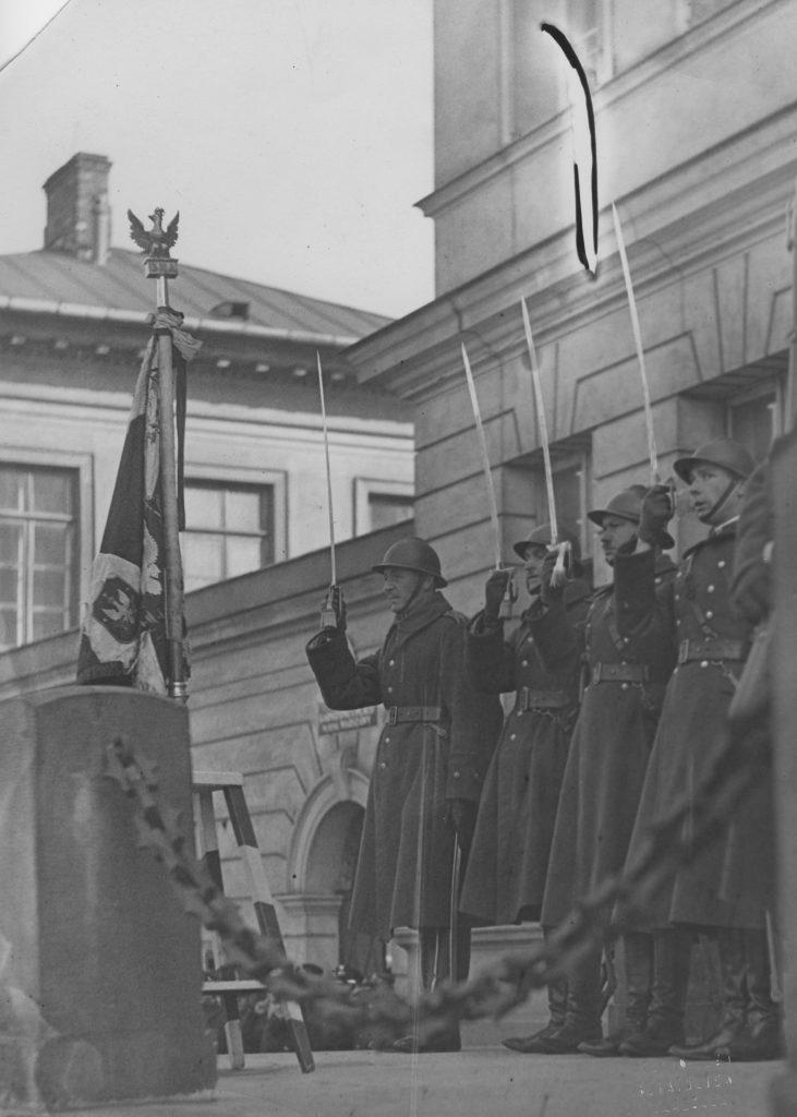 grupa żołnierzy salutujących szablami, w tle budynek