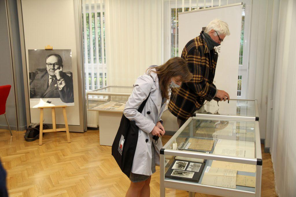 dwoje ludzi pochyla się nad gablotami z eksponatami wystawy, po lewej w tle portret bohatera wystawy