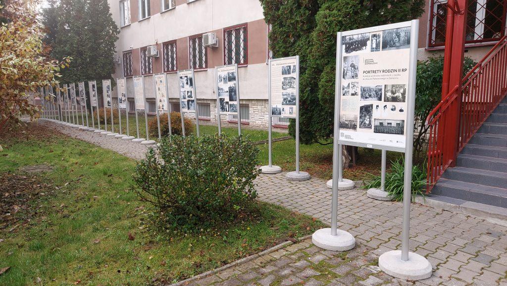 plansze wystawy w rzędzie przed budynkiem.