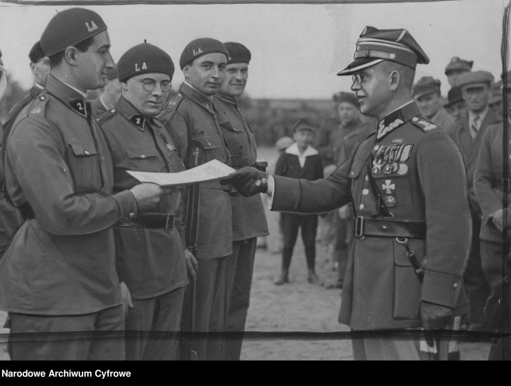 mężczyzna w mundurze z medalami wręcza niższym rangą żołnierzom w beretach dokument