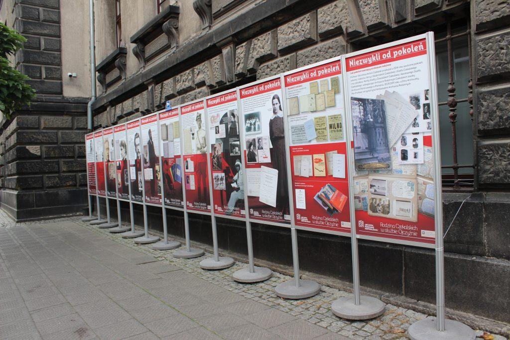 plansze wystawy ustawione w rzędzieprzed budynkiem