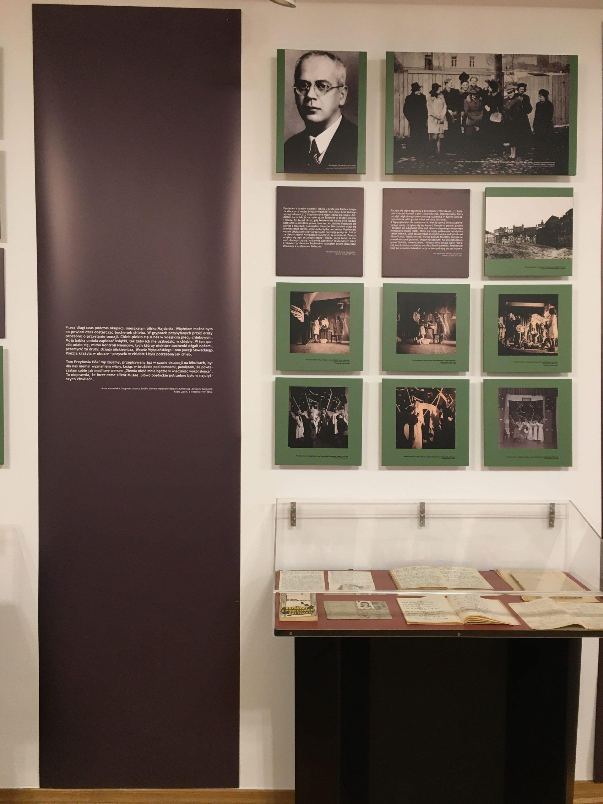 fragment wystawy - na ścianie zdjęcia, plansze i element ozdobny z cytatem, poniżej stoi witrynka z eksponatami