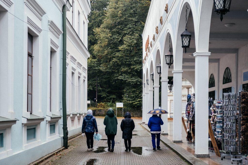 4 osoby idące przejściem pomiędzy dwoma białymi budynkami w deszczową pogodę