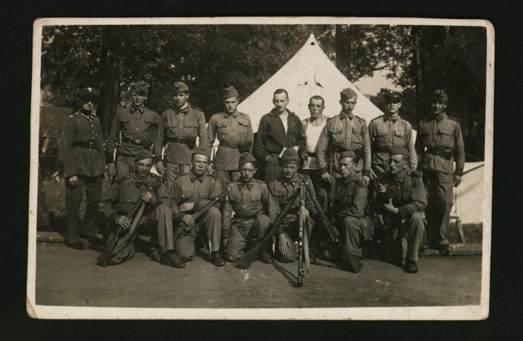 grupa żołnierzy pozująca do zdjęcia przed namiotem