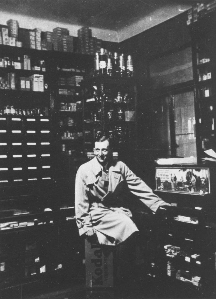 mężczyzna w fartuchu siedzący na stołku wśród apyecznych półek na czarno-białej fotografii
