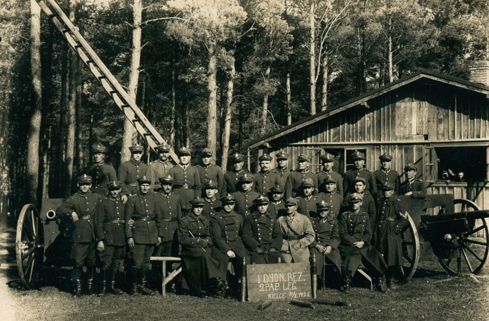 grupa żołnierzy w mundurach w fotografii pozowanej z dwoma działami drabiną i koszarami i lasem w tle