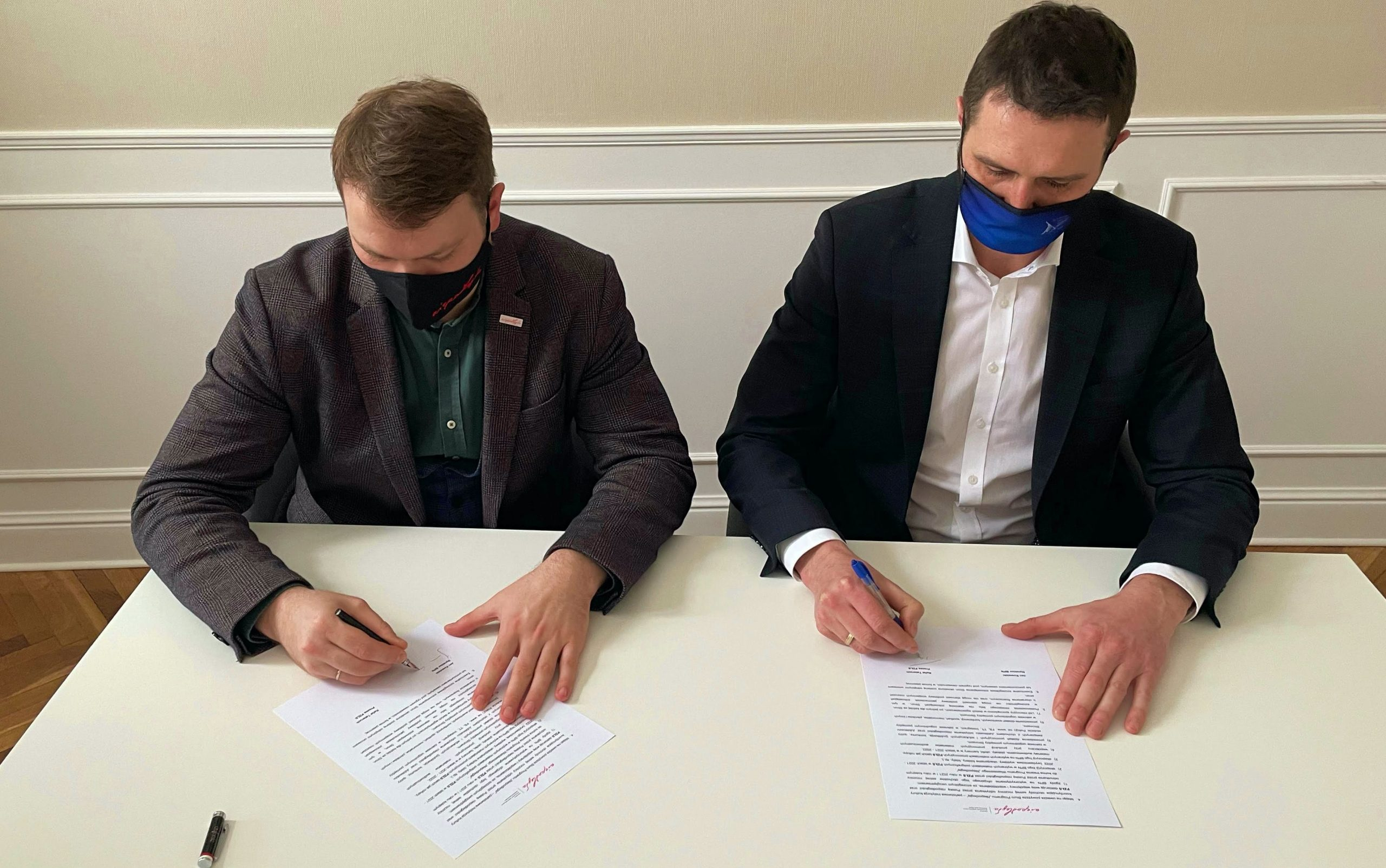 Dwóch mężczyzn siedzących przy stole i podpisujących dokumenty