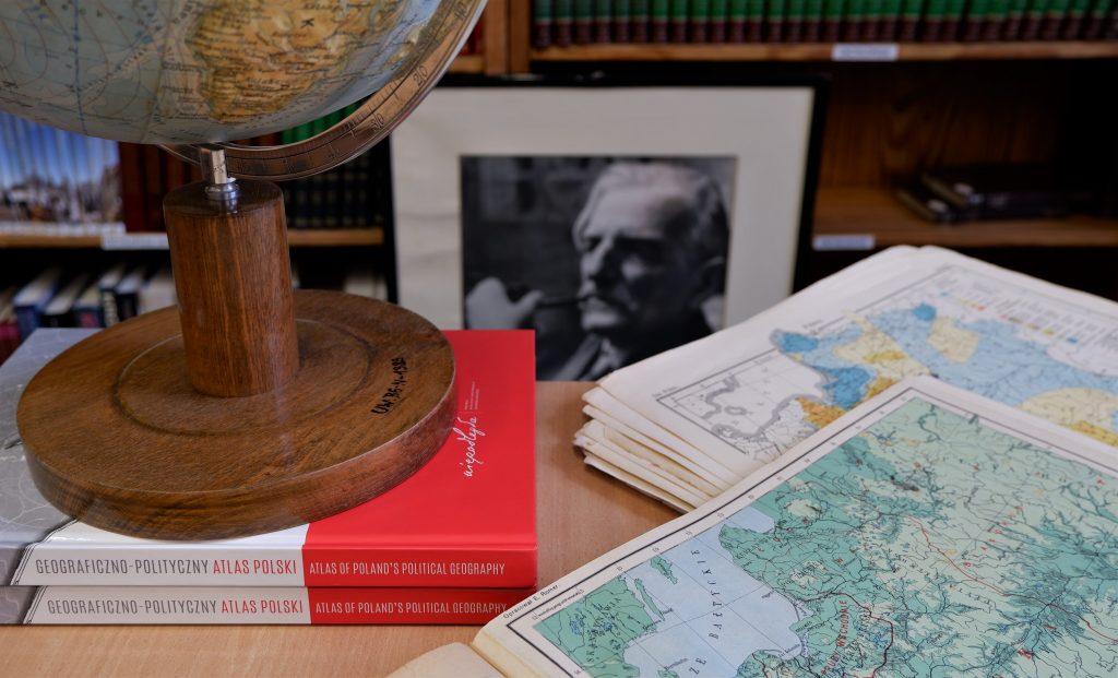 globus i rozłożone mapy, w tle czarno-biały portret Romera