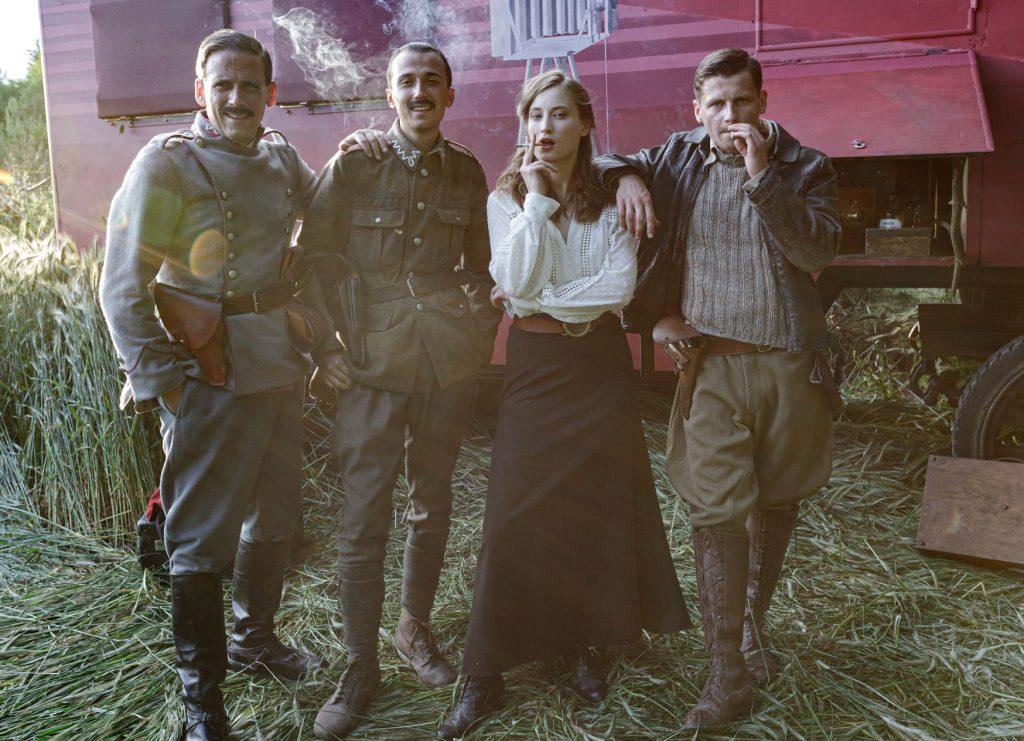 czwórka aktorow przed wozem fotograficznym - elementem scenografii filmowej