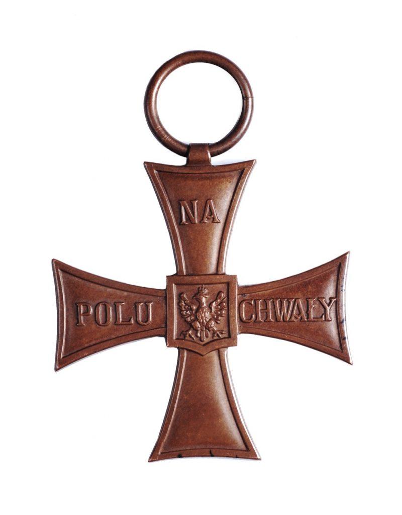 krzyż odlany z metalu z orłem na przecięciu ramion i na ramionach napisem Na polu chwały