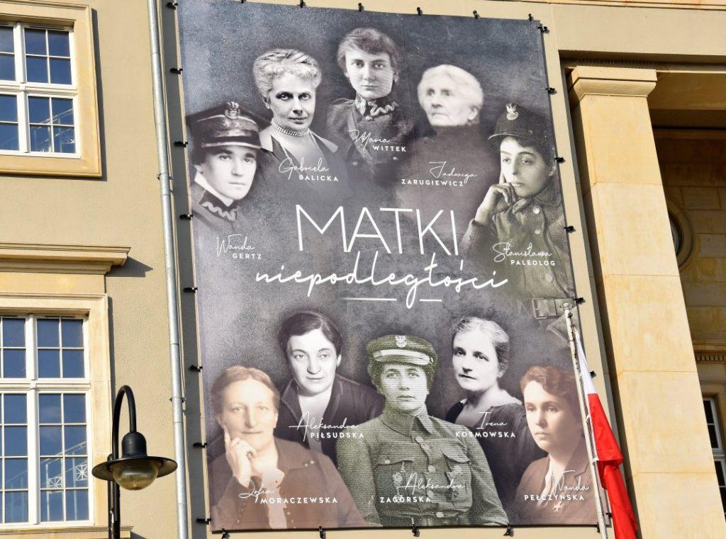 baner z 10 podpisanymi postaciami kobiecymi zawieszony na budynku