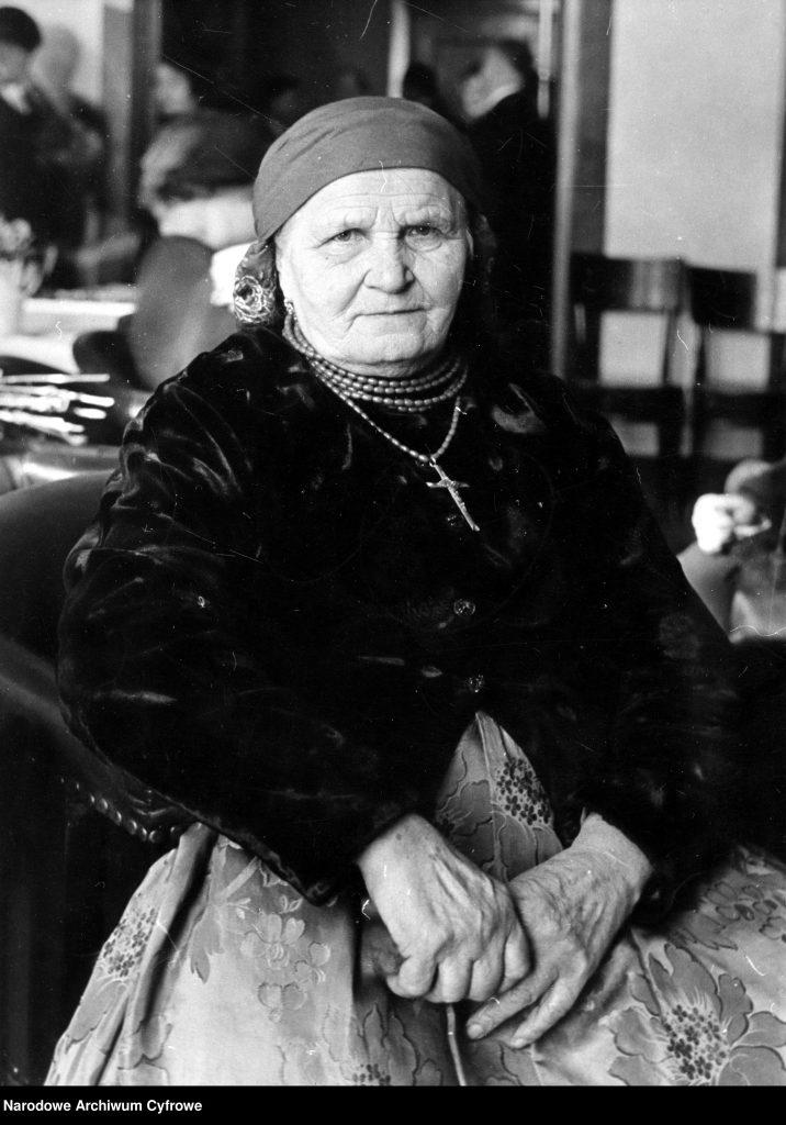 zdjęcie portretowe siedzącej starszej kobiety w śląskim stroju ludowym z krzyżem na piersi