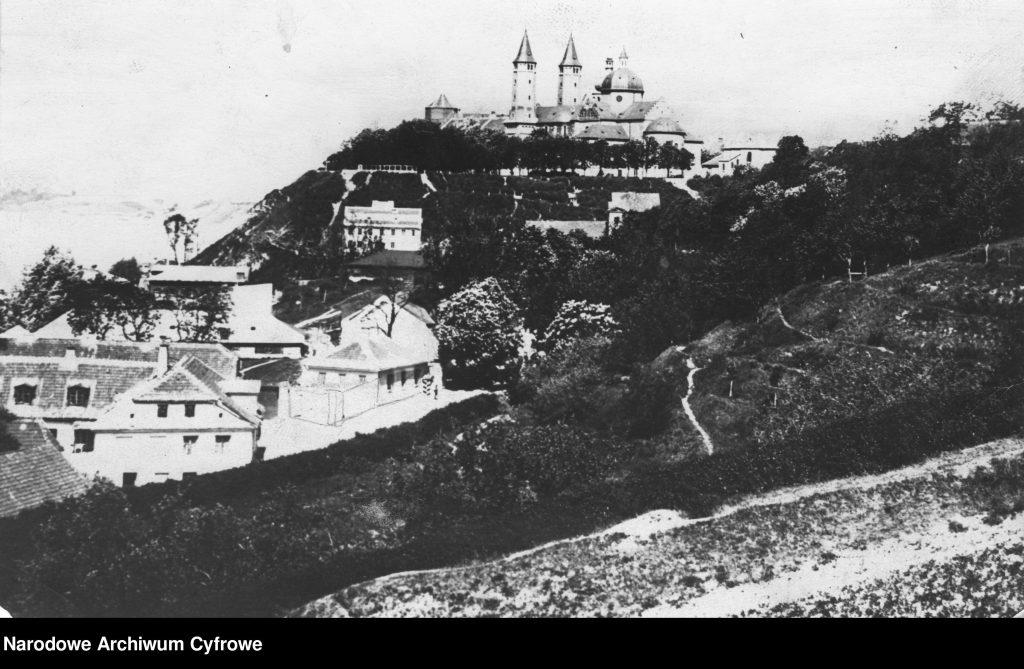 widok na okazały kościół na wzgórzu, po prafej dachy zabudowy miejskiej