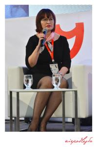 zdjęcie kobiety siedzącej na scenie z mikrofonem