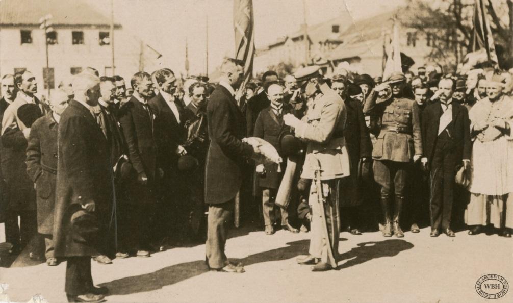 przed tłumem zgromadzonym na rynku uroczysty sztandar, a przed nim dwóch mężczyzn - po lewej trzyma poduszkę z symbolami miasta, po prawej Piłsudski do poduszki przypina order