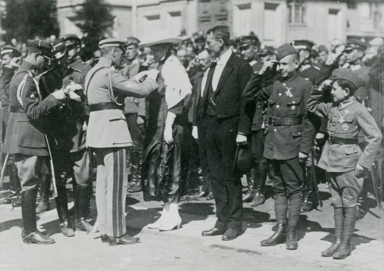 ludzie na rynku w oficjalnych strojach. Odwrócony tyłem Piłsudski przypina order jednemu z oczekujących