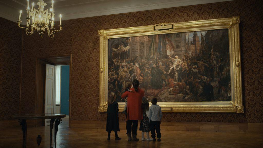matka z czwórką dzieci w ozdobnej sali przed obrazem matejki konstytucja 3 maja