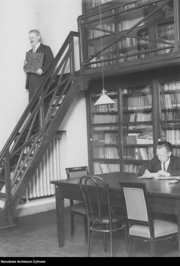 fragment pomieszczenia ze stołem, regałami i antresolą a także dwoma mężczyznami przy pracy naukowej