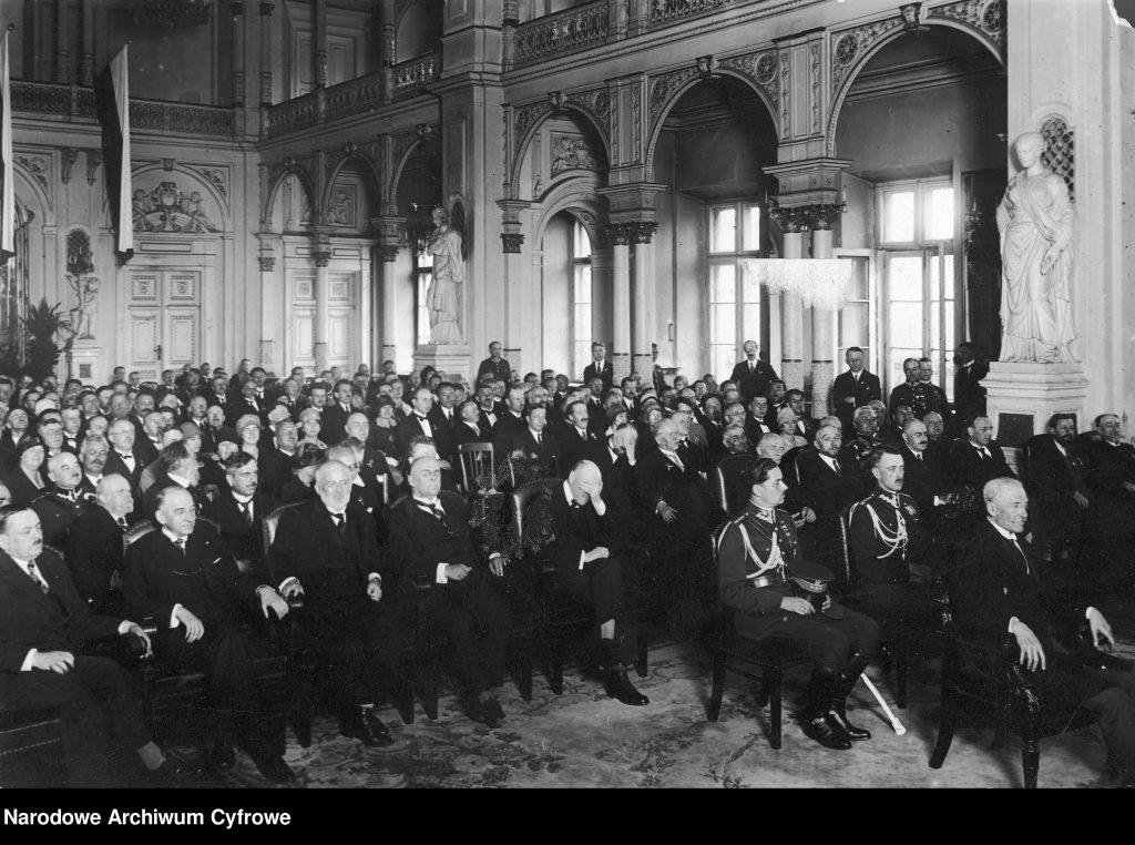 grupa elegancko ubranych ludzi sziedząca na krzesłach w ozdobnej sali