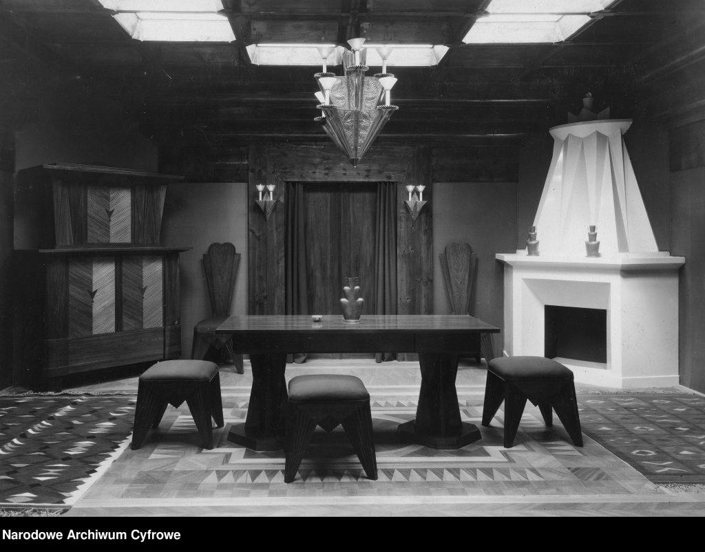wystój wnętrza - komoda, stół z krzesłami, kominkiem, dywanem i ozdobnym żyrandolem