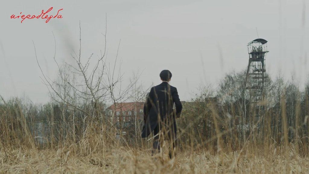 postać chłopaka która idzie w kierunku jakiegoć budynku i szybu