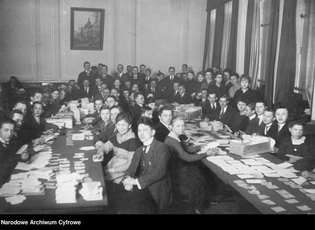 ludzie usadzeni przy długich stołach zarzuconych kartkami papieru