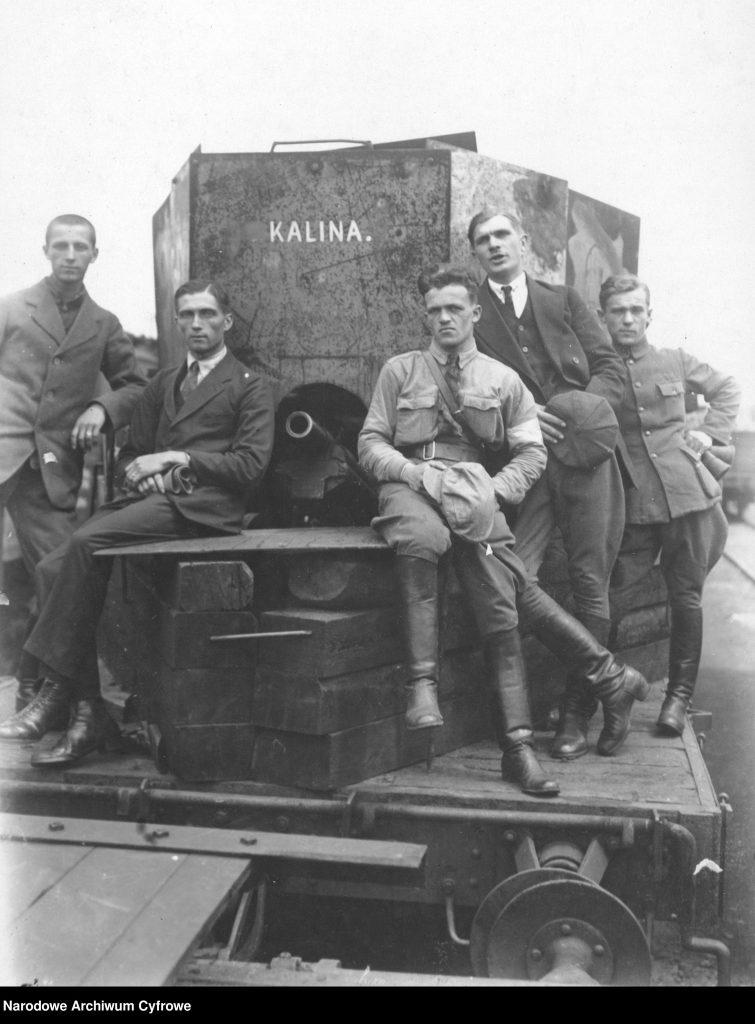pięciu mężczyzn pozuje przy pociągu pancernym z namalowaną nazwą Kalina