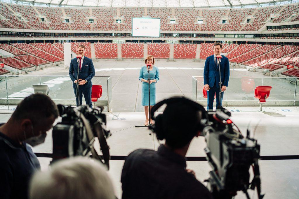 trzy elegancko ubrane osoby przed mikrofonami, w tle trybuny PGE Narodowego, na pierwszym planie kamery