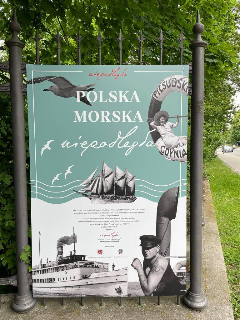 plansza tytułowa wystawy rozwieszona na płocie Łazienek