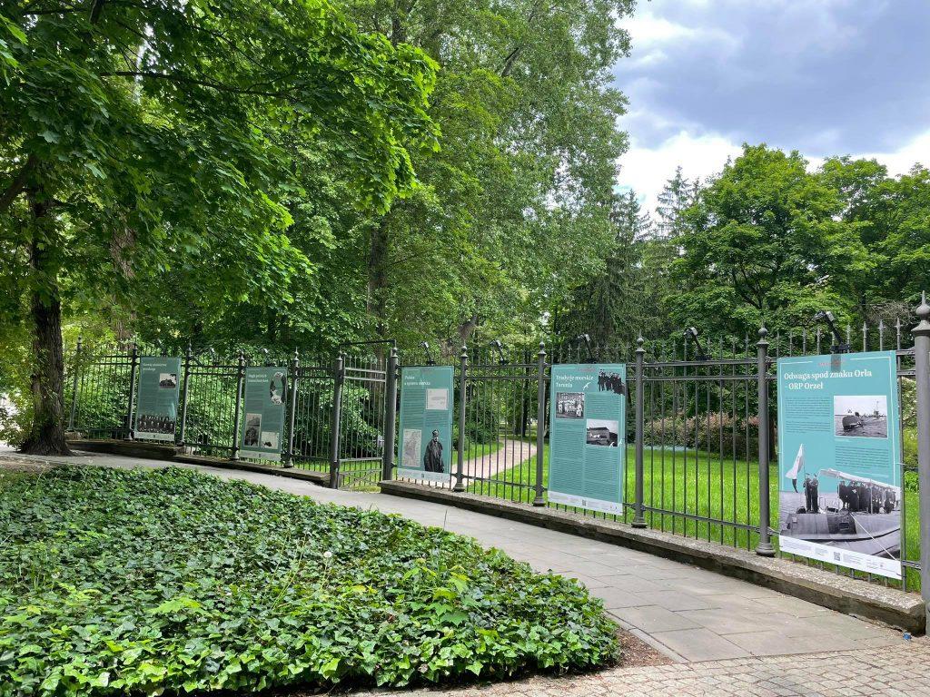 plansze wystawy rozwieszone w równych odstępach na płocie Łazienek