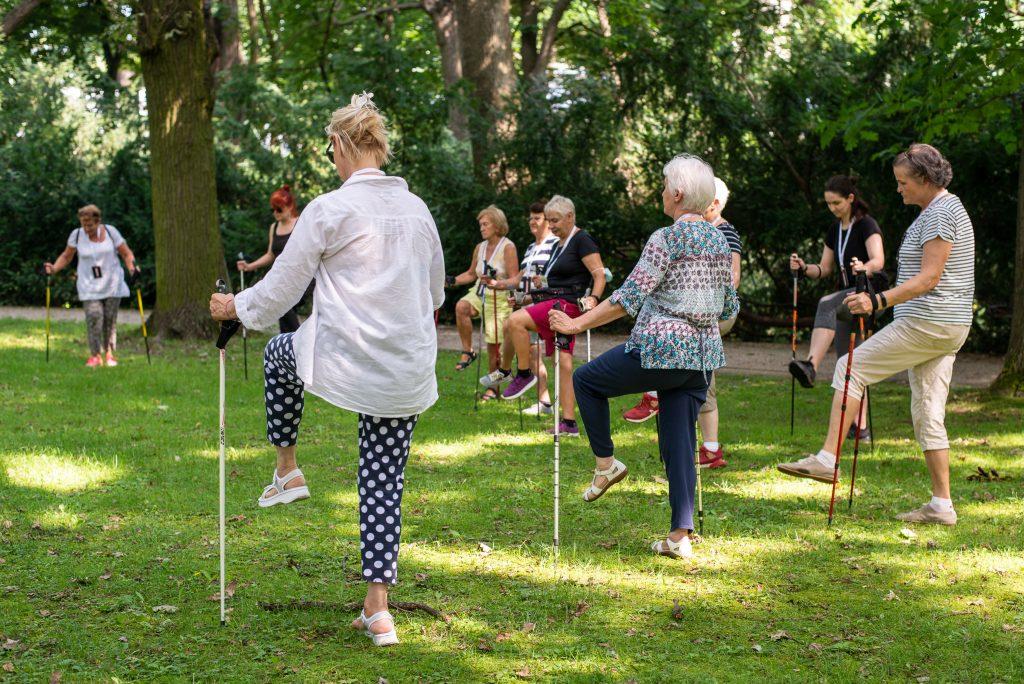 seniorki z wbitymi kijami Nordic Walking i uniesionym kolanem podczas ćwiczeń