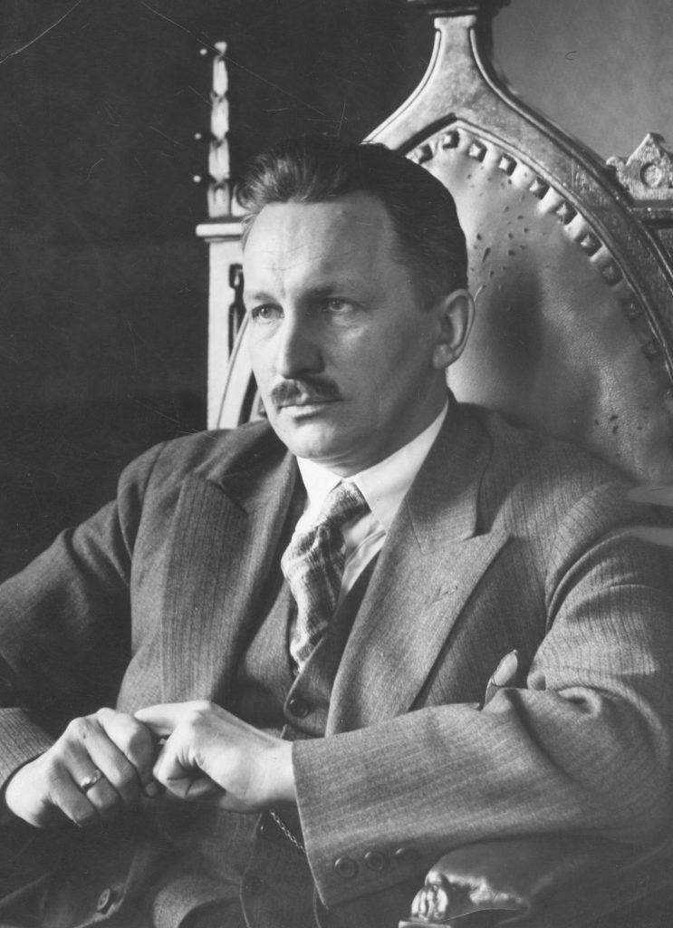mężczyzna w garniturze siedzący na ozdobnym krześle