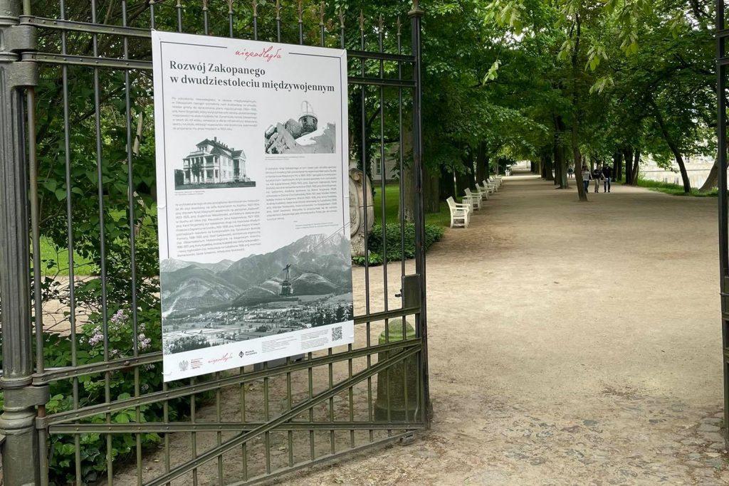 """plansza wystawy zatytułowana """"Rozwój Zakopanego w dwudziestoleciu"""" na bramie Łazienek"""