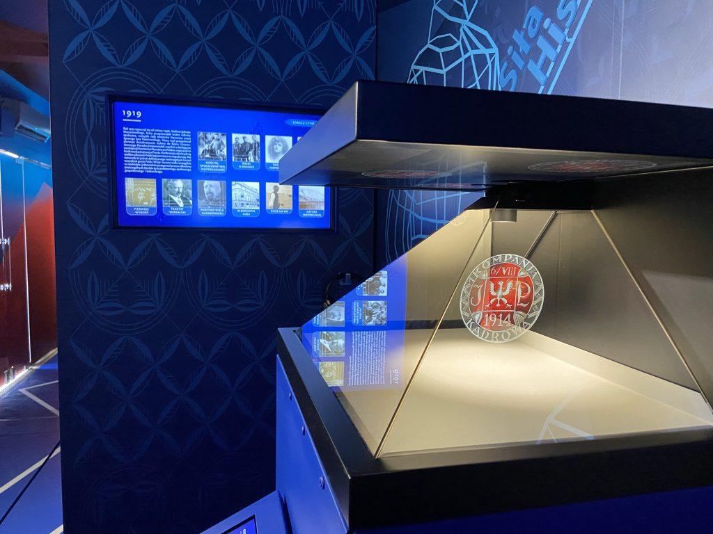 zdjęcie ukazujące piramidę holograwiczną i ekran multimedialny i fragment dekoracji graficznej wnętrza tira