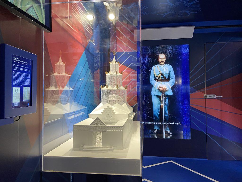 zdjęcie ukazujące makietę pawilonu i hologram marszałka multimedialny i fragment dekoracji graficznej wnętrza tira
