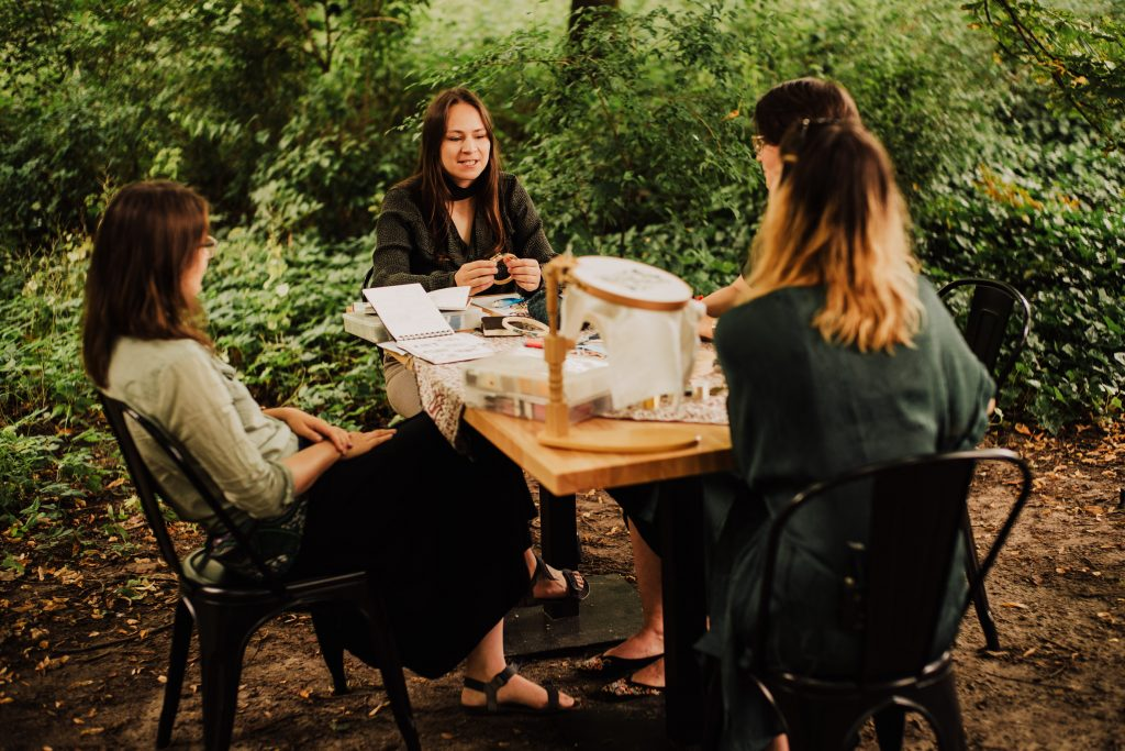 cztery kobiety haftujące przy stole