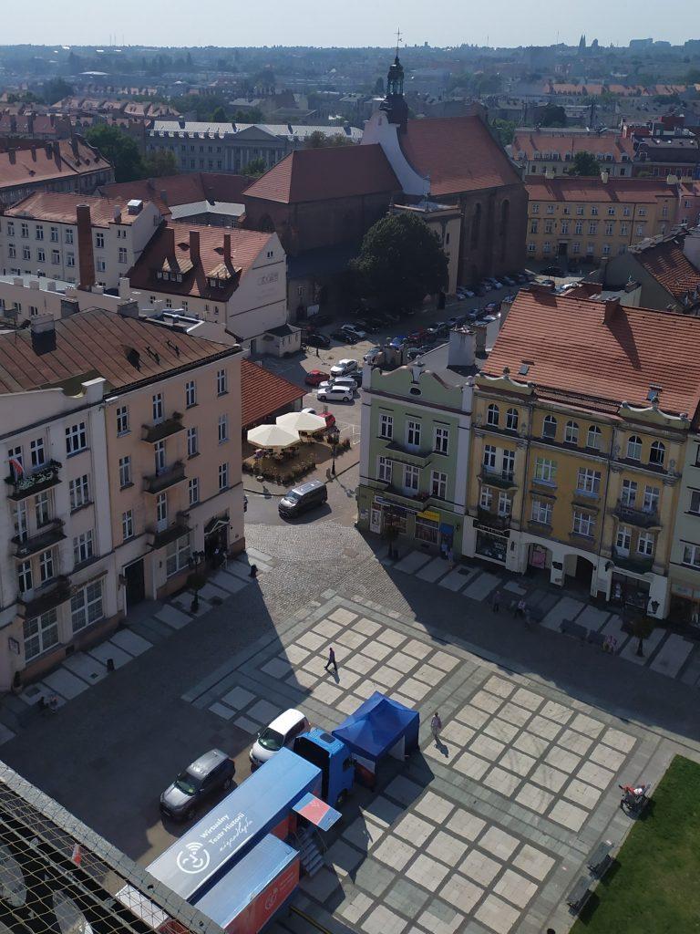 widok z góry na rozstawiony samochod stojący na rynku pomiędzy kamieniczkami, w tle kościół i zabudowa miejska Kalisza