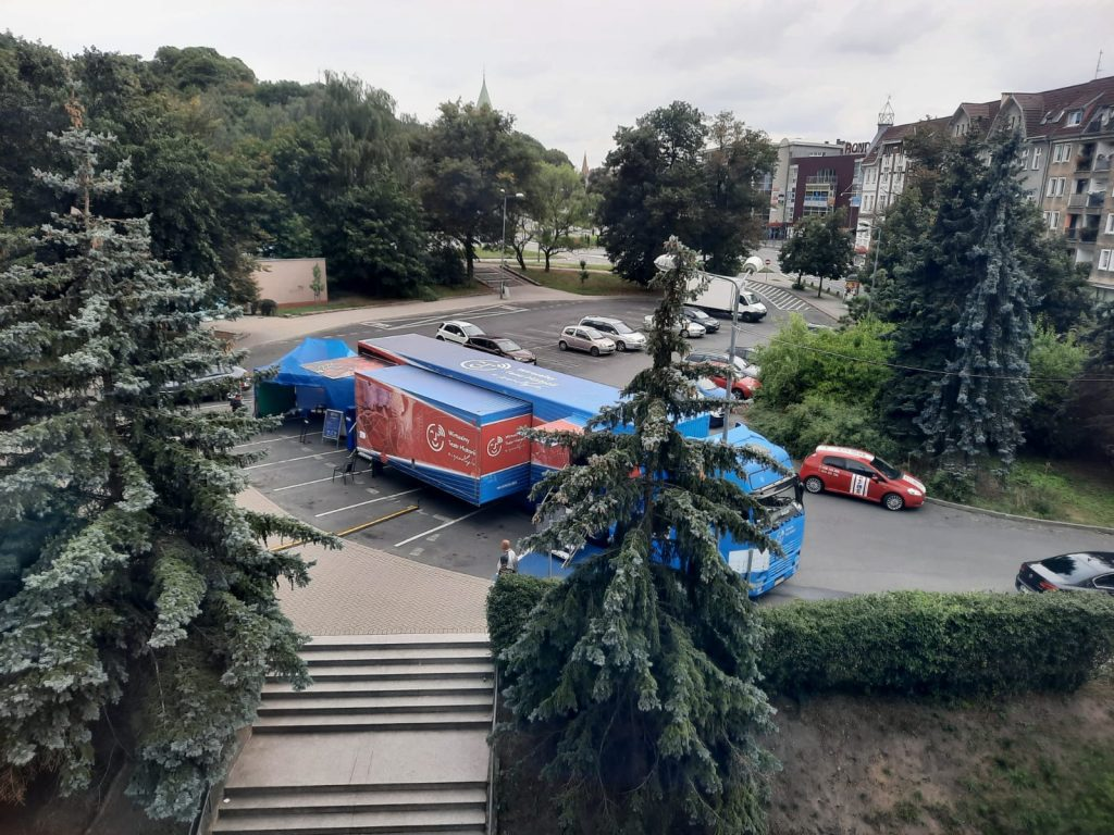 rozstawiony samochód ciężarowy z wystawą zaparkowany na miejskim parkingu