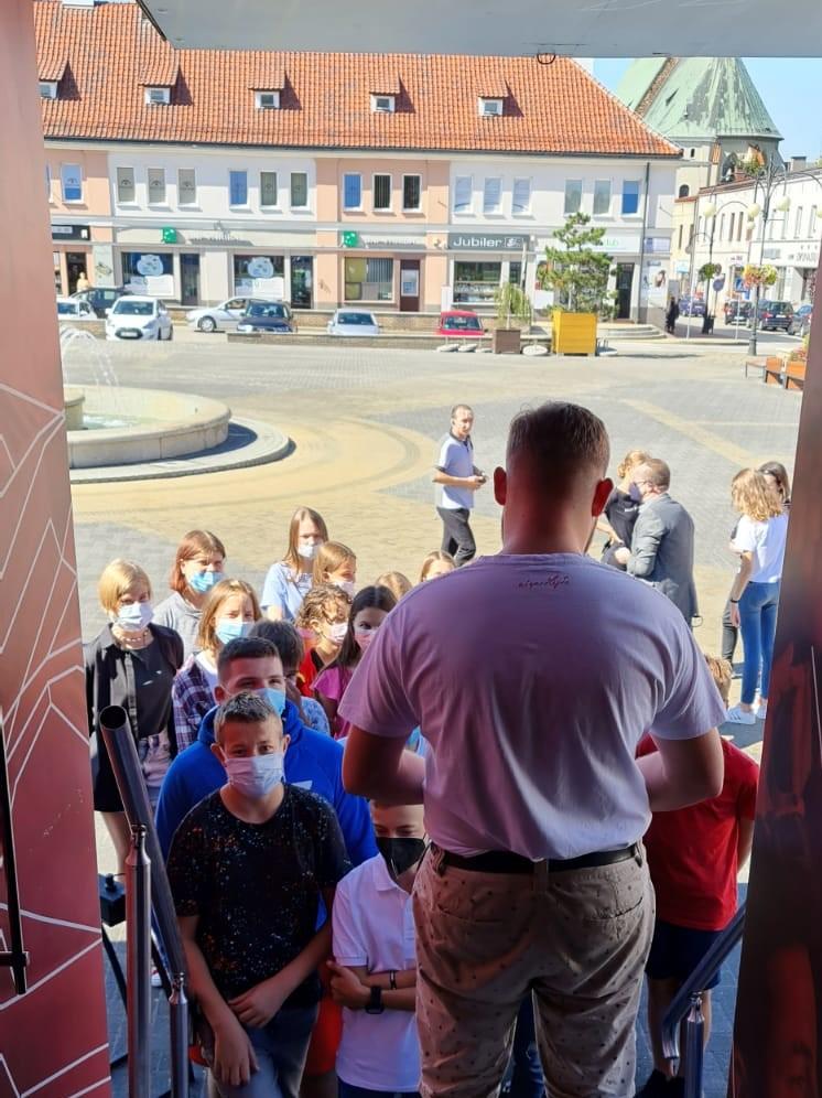 mężczyzna stoi w wejściu do teatru, odwrócony tyłem do widza a prodzem do grupy dzieci w maseczkach czekających na wejście, w tle pierzeja kamienic i po prawej sylwetka kośćioła