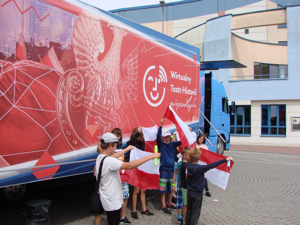 grupa dzieci z biało-czerwonymi flagami przed autobusem WTH, w tle budynek MOSiR