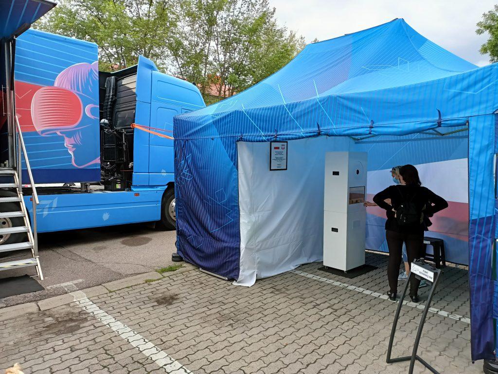 rozstawiony bus i namiot z fotobudką na parkingu, w tle drzewa
