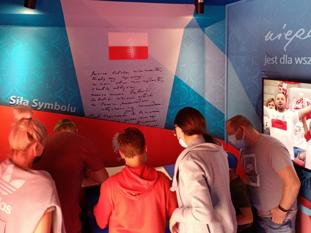 pięcioro ludzi pochyla się nad księgą w której jeden mężczyzna dokonuje wpisu, w tle grafiki wnętrza WTH
