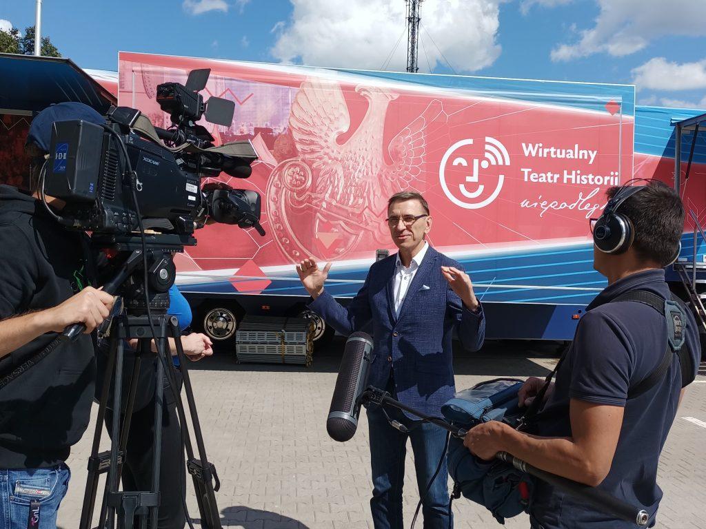 przed oklejoną ciężarówką stoi elegancki mężczyzna i opowiada do kamery i dziennikarza
