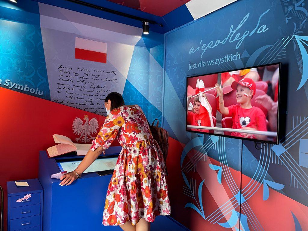zdjęcie przedstawia kobietę w sukience oglądającą multimedialną ekspozycję w autokarze zaadaptowanym na inteaktywną przestrzeń wystawienniczą