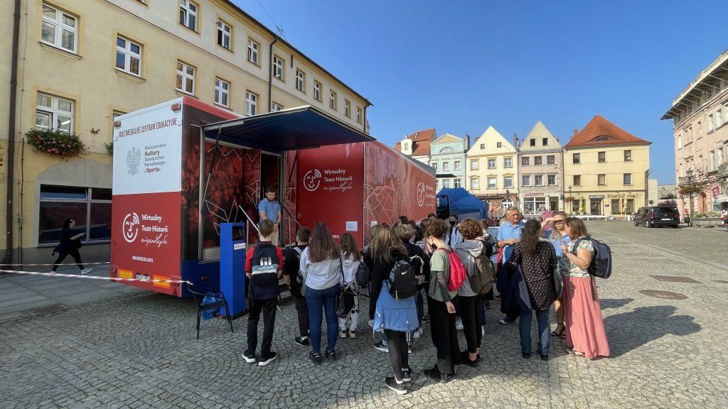 autobus z wystawą stojący na tle kamieniczek, przed wejściem tłum dzieciaków