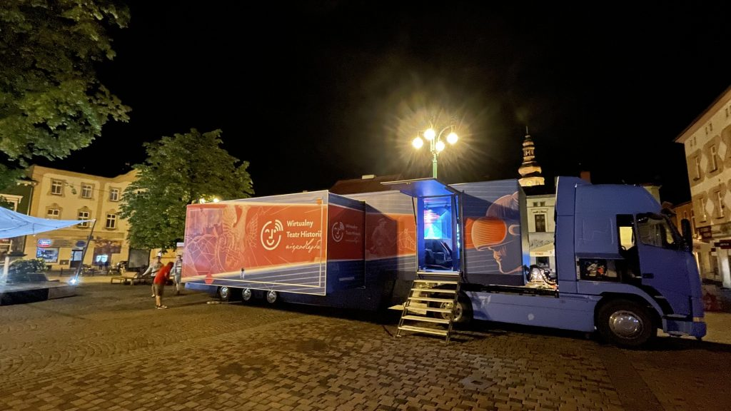 rozłożony bus na miejskim rynku nocą, w tle zabytkowa wieża